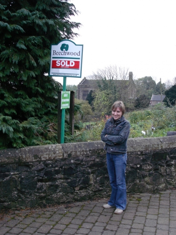 Photo of Emma under the Sold sign